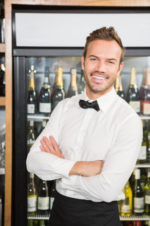 arms folded: Handsome barman with arms folded in a pub