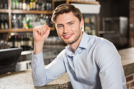 leaning on elbows: Handsome man leaning his elbow on the counter in a pub