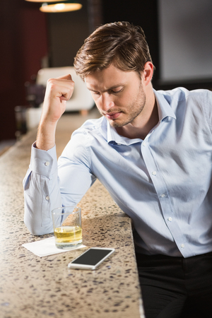 leaning on elbows: Tired man leaning his elbow on the counter in a pub Stock Photo