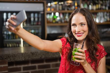 tomando refresco: Mujer bonita que toma una autofoto con su cóctel en un bar