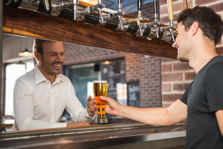 Apuesto barman dando una pinta para un cliente en un bar