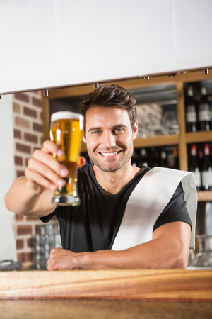 pint: Handsome barman holding a pint of beer in a pub