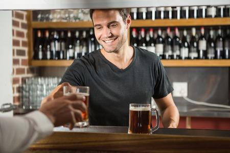 Hermoso bar tierno dando una pinta al cliente en un pub