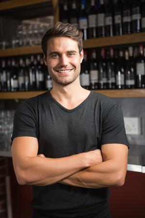 Apuesto oferta de la barra de pie detrás del mostrador de un bar