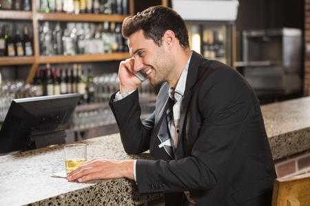 beau mec: Bel homme ayant un whisky et un appel t�l�phonique dans un pub