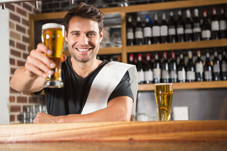 bartender: Handsome barman holding a pint of beer in a pub