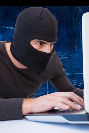 anonym: Hacker using laptop to steal data Stock Photo