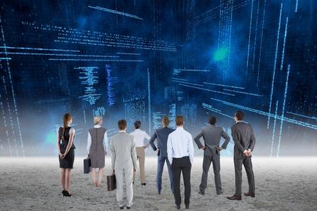 analyzing: Business team analyzing data on futuristic screen