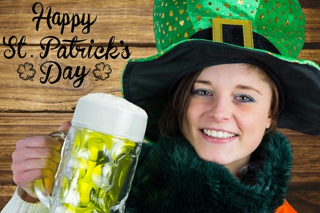 st patty day: Woman holding beer next to st patricks day greeting on wooden background