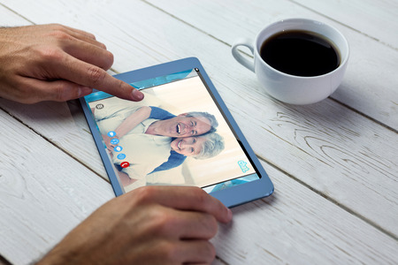 remix: Music app against person using tablet on wooden table Stock Photo