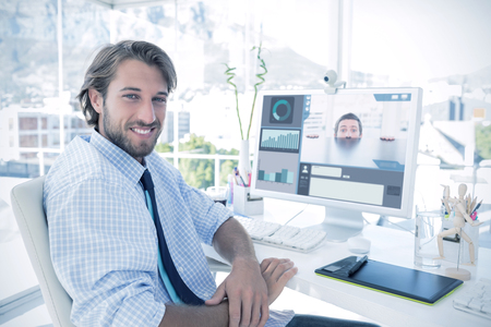 artists mannequin: Nervous businessman peeking over desk against smiling designer sitting at his desk