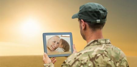 Soldier using tablet pc against desert scene photo