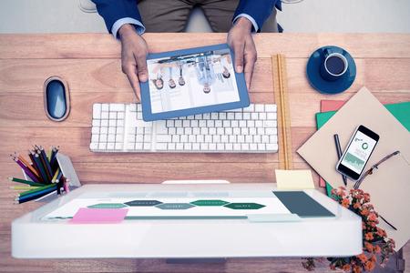 mid adult men: Business graphs against businessman holding digital tablet while sitting at computer desk Stock Photo