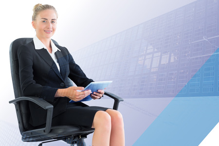 swivel: Businesswoman sitting on swivel chair with tablet against skyscraper Stock Photo