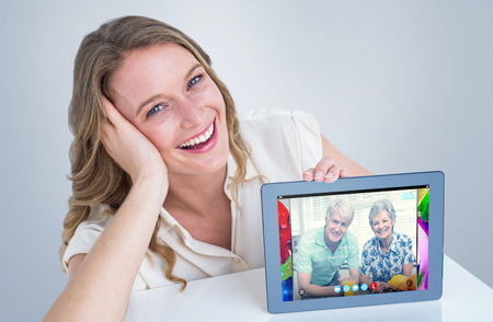 video chat: Woman showing tablet pc  against senior couple using video chat Stock Photo