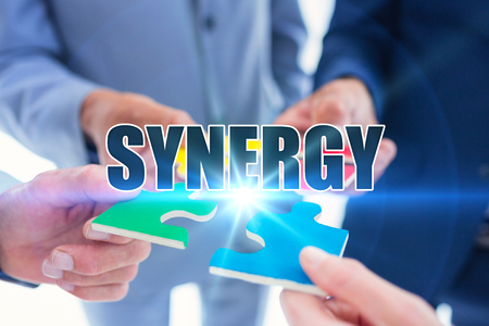 sinergia: The word synergy against business colleagues holding piece of puzzle