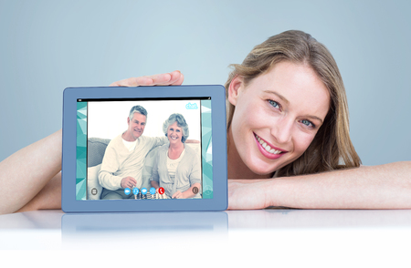 Woman showing tablet pc  against seniors using video chat photo