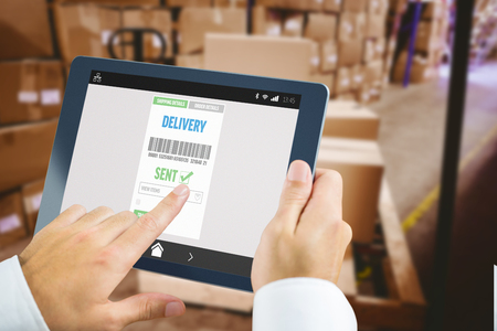 storage: Man using tablet pc against warehouse with cardboard boxes