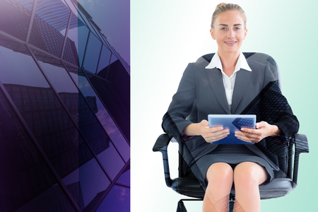 swivel chair: Businesswoman sitting on swivel chair with tablet against skyscraper Stock Photo