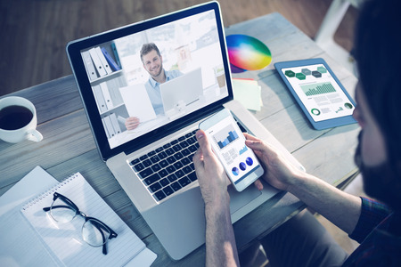 high angle view: Handsome man working at his desk on laptop smiling at camera against high angle view of editor using smartphone and laptop Stock Photo
