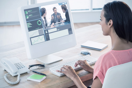 charismatic: Businesswoman using computer at desk in creative office against charismatic chairman talking with his team
