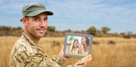 Soldado usando la pc de la tableta contra el paisaje con animales
