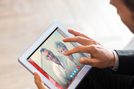 using tablet: Music app against businessman using tablet Stock Photo