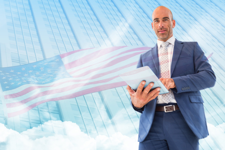 sky scraper: businessman using a tablet and smiling at the camera  against american flag against sky scraper