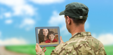 Soldier using tablet pc against road leading out to the horizon photo