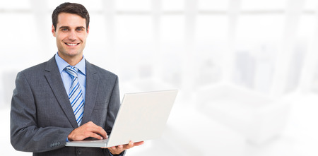 corporate buildings: Portrait of smiling businessman using laptop against modern room overlooking city Stock Photo