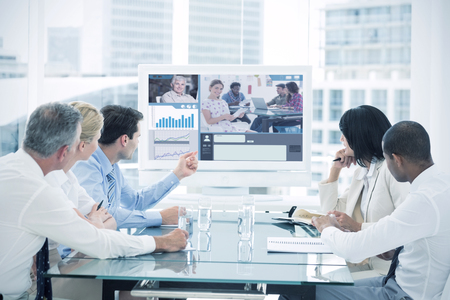 Editor holding tablet and smiling as team works behind her against business people looking at blank whiteboard in conference room Banco de Imagens