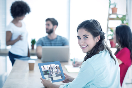 Smiling businesswoman using tablet against business people in conference meeting