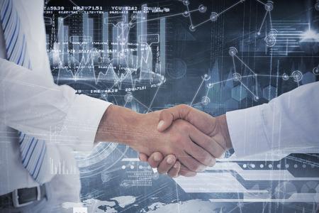 mid adult men: Close-up shot of a handshake in office against hologram background