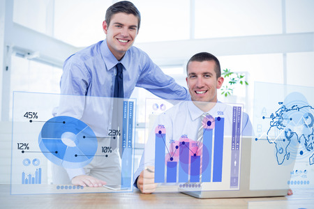 digitally generated image: Businessmen using laptop against digitally generated image of pie chart and bar graph