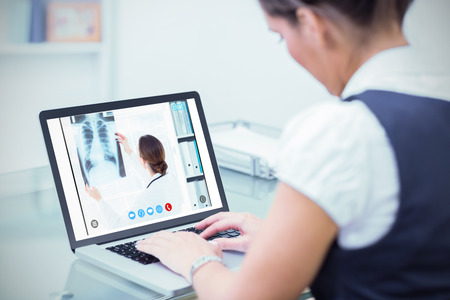 online service: Female doctor studying Xray against business worker using laptop at desk
