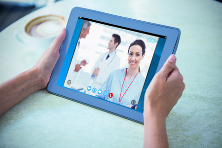 video chat: View of video chat app against person holding tablet computer at table in cafe Stock Photo