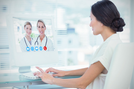 online service: Blonde doctors standing together against young businesswoman using computer in office