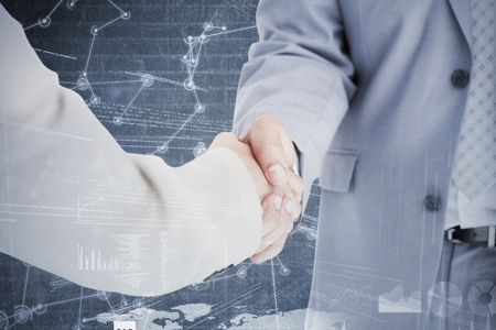 mature adult: People in suit shaking hands against hologram background