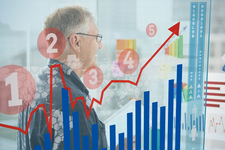 against the flow: Graph  against smiling businessman looking flow charts on the wall
