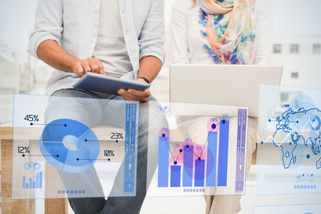 business partner: Digitally generated image of pie chart and bar graph against casual designers sitting on wooden desk and using devices