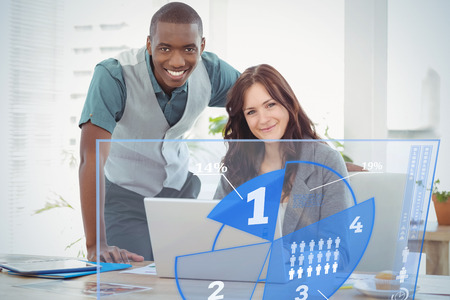 coworker: Futuristic interface pie chart interface  against portrait of smiling businesswoman working on laptop with coworker at desk Stock Photo