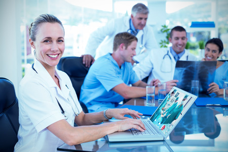 video chat: Beautiful smiling doctor typing on keyboard with her team behind against view of video chat app
