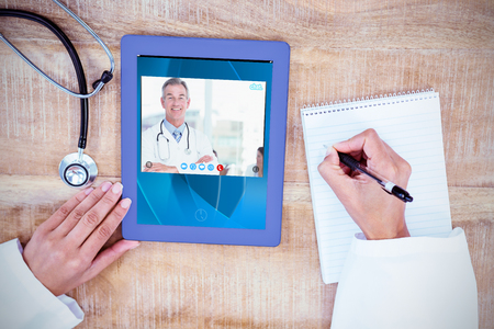 View of video chat app against doctor writing on a notepad Reklamní fotografie