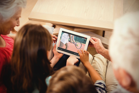 70s tennis: View of lecture app against family using tablet Stock Photo