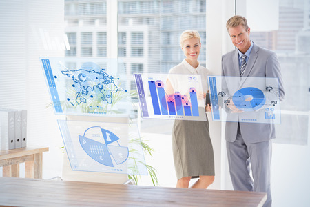 well dressed woman: Digitally generated image of pie chart and bar graph against smiling business partners looking at camera