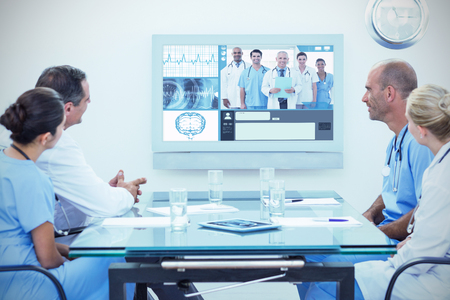 ribcage: Team of doctors having a meeting against team of smiling doctors looking at camera