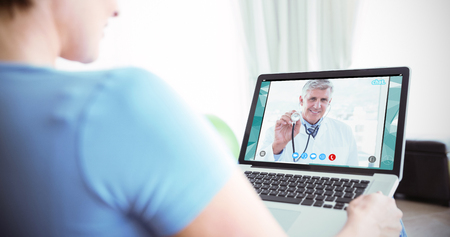 video chat: Pregnant woman using her laptop against view of video chat app