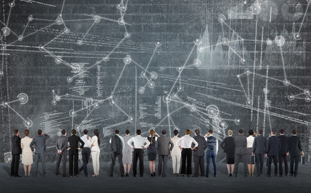 Rear view of multiethnic business people standing side by side against hologram background Stock Photo