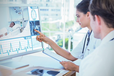 hospitalized: Doctor pointing at the screen of a computer against white background with vignette
