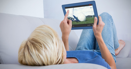 kick ball: Blonde woman using her tablet on the couch against football player about to kick ball